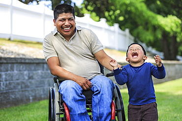 Hispanic man with Spinal Cord Injury in wheelchair with his son laughing in lawn