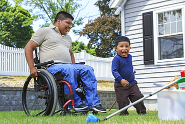 Hispanic man with Spinal Cord Injury in wheelchair with his son preparing to wash a car