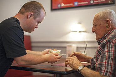 Waiter with Down Syndrome serving food to customer in a restaurant