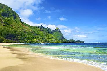 View Of The Coastline Of Kauai With Rugged, Green Mountains And A Sand Beach; Wailua, Kauai, Hawaii, United States Of America