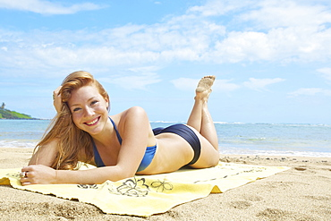 Portrait Of A Young Woman In A Bikini Laying On A Towel On The Beach With The Ocean In The Background; Wailua, Kauai, Hawaii, United States Of America