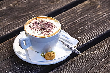 Cappuccino by an Italian cafe on wooden table, served with a small biscuit; Hexham, Northumberland, England