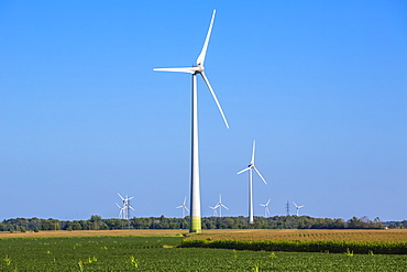Wind turbines on farmland with a farm field in the foreground; Saint Remi, Quebec, Canada