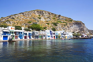 Klima village with white houses and colourful accents along the water's edge; Klima, Milos Island, Cyclades, Greece