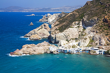 Fyropotamos Village with boats in the small harbour and a view of the rugged coastline; Fyropatamos, Milos Island, Cyclades, Greece