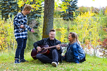 A young man with Down Syndrome playing a tambourine while his father plays a guitar and his mother sings along while enjoying each other's company in a city park on a warm fall evening: Edmonton, Alberta, Canada