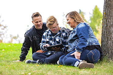 A young man with Down Syndrome learns a new program on a tablet with his father and mother while enjoying each other's company in a city park on a warm fall evening: Edmonton, Alberta, Canada
