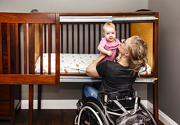A paraplegic mother lifting a baby from a customized side-opening crib that allows her to put her baby down for a nap from her position in a wheelchair: Edmonton, Alberta, Canada