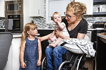 A paraplegic mom in a wheelchair talking with her daughter and holding her baby in her lap while working in her kitchen; Edmonton, Alberta, Canada