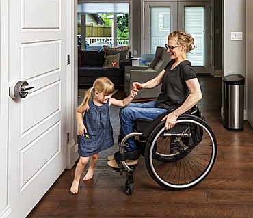 A paraplegic mother dancing with her daughter in the kitchen using her whellchair: Edmonton, Alberta, Canada