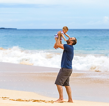 Father holds his baby daughter in the air as he stands on the beach next to the ocean; Maui, Hawaii, United States of America