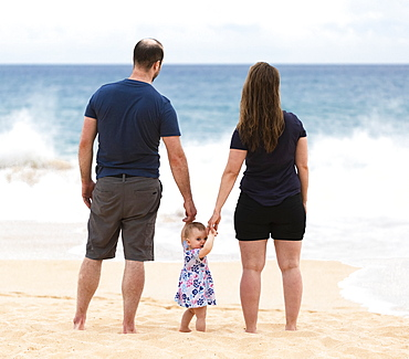 Mother and father hold the hands of their baby daughter as they stand looking out at the ocean; Maui, Hawaii, United States of America