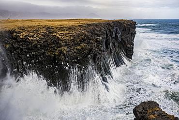 Waves splash up against the cliffs along the coast; Arnarstapi, Snaefellsnes, Iceland