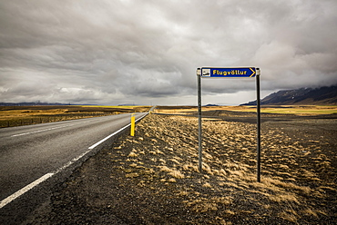 Road and tundra landscape with roadside airport sign; Iceland