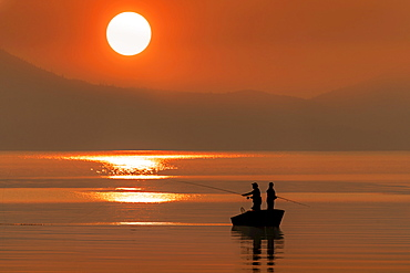 Silhouetted anglers standing in a boat fishing for salmon at sunset; Juneau, Alaska, United States of America