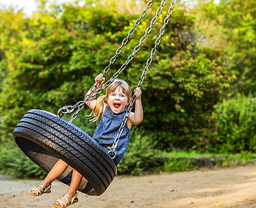 A young girl makes a silly face as she swings on a tire swing; Edmonton, Alberta, Canada