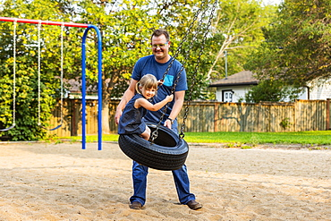 A father pushes his daughter on a tire swing at a playground; Edmonton, Alberta, Canada