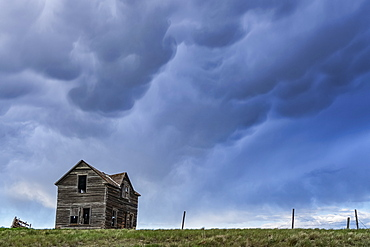 Old farmstead on the prairies under a stormy sky; Saskatchewan, Canada