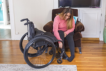 Woman with Spinal Cord Injury putting on shoes
