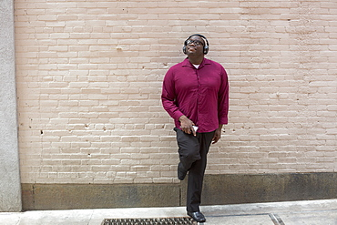 Man with ADHD standing against a wall listening music