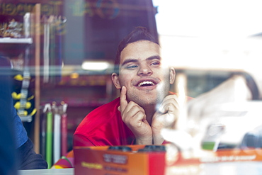 Middle Eastern man with Down Syndrome smiling at work