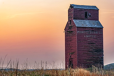 Abandoned and weathered grain elevator at sunset on the Canadian Prairies; Val Marie, Saskatchewan, Canada