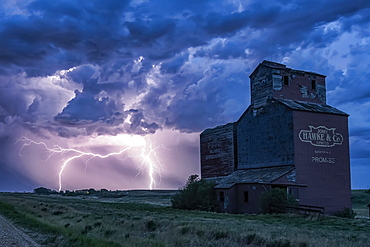 Grain elevator in a dramatic thunderstorm with dark clouds and lightning strikes in the distance; Saskatchewan, Canada