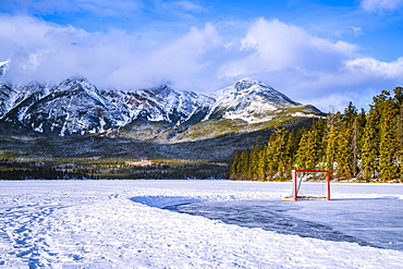Frozen Pyramid Lake with hockey net on a cleared ice rink in winter, Jasper National Park; Alberta, Canada