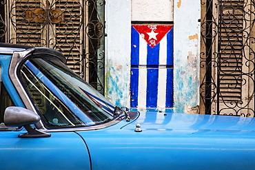 Cuban flag and blue car on the streets of Havana; Havana, Cuba