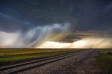 Dark storm clouds over railroad tracks in a field with rain falling in the distance; Marquis, Saskatchewan, Canada