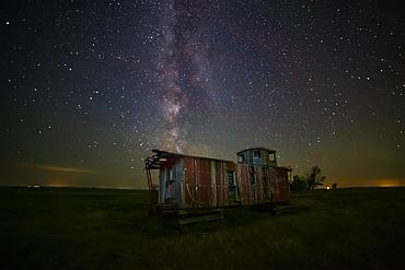 Old caboose at nighttime under a bright, starry sky; Coderre, Saskatchewan, Canada