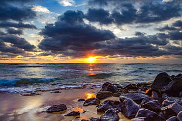 Sunrise over the Pacific Ocean from the rocks on the shore of Lydgate Beach and dark clouds overhead; Kapaa, Kauai, Hawaii, United States of America