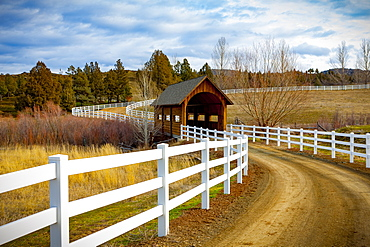 Covered bridge over a river in the countryside with dirt road; Oregon, United States of America