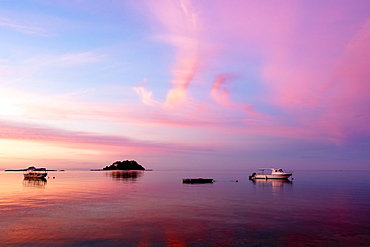 Sunrise over the South Pacific with boats anchored off the shore; Malolo Island, Fiji