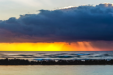 Dramatic sunrise over Lydgate Beach, breakwater and the ocean from the coast of Kauai with dark storm clouds and a distant rainfall; Kapaa, Kauai, Hawaii, United States of America