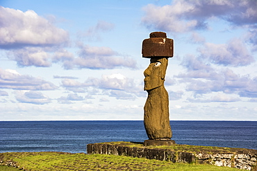 A single moai on a blue background of sky, clouds and ocean; Easter Island, Chile