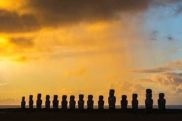 The fifteen moais of Tongariki silhouetted against the brightly coloured sky of sunrise; Easter Island, Chile