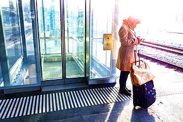 A woman stands with her suitcase on the platform of a train station beside the tracks and uses her smart phone; St. Gallen, St. Gallen, Switzerland