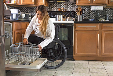 Woman with Spinal Cord Injury arranging dishwasher