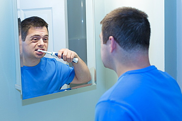 Man with Down Syndrome brushing teeth in bathroom