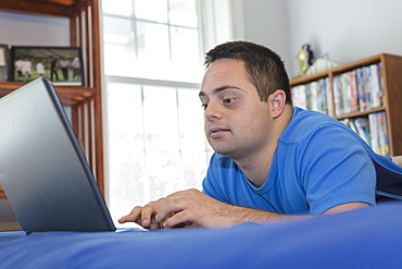 Man with Down Syndrome lying on bed using a laptop