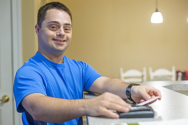 Man with Down Syndrome holding a credit card