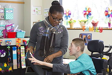 Teen with Holoprosencephaly and assistant at school