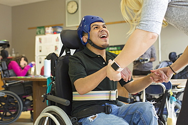 Boy with Spastic Quadriplegic Cerebral Palsy using using his helmet and strap