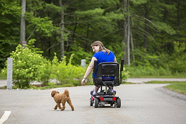 Young Woman with Cerebral Palsy playing with her dog while sitting on her scooter