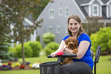 Young Woman with Cerebral Palsy riding the scooter with her dog