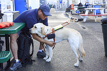 Blind man sitting with his service dog