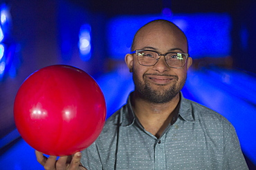 African American man who has Down Syndrome holding a bowling ball