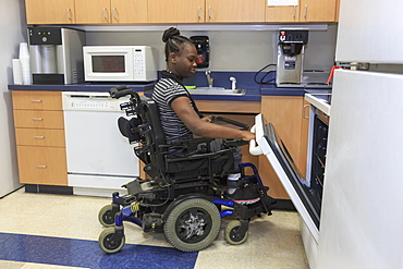 Teen with Cerebral Palsy using oven in the kitchen