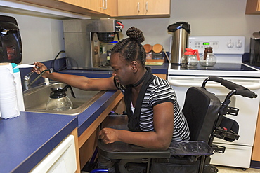 Teen with Cerebral Palsy working in the kitchen